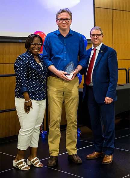 Undergraduate Advising Center Advisor Carsten Holm, center, was presented the 2019 Advisor of the Year Award by Vice Provost for Undergraduate Studies DeAngela Burns-Wallace, left, and Chancellor Douglas A. Girod, right.