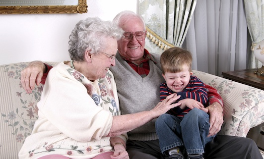 An older couple snuggle with a toddler