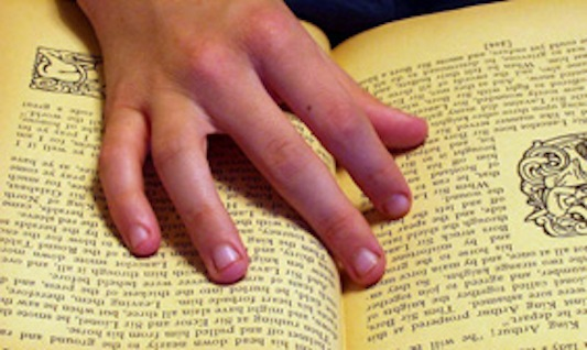 Child's hand on book