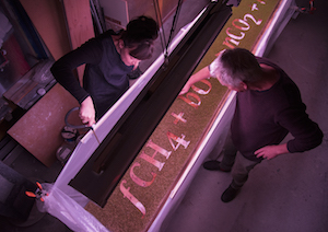 In darkened room, two artists work on a piece for Big Botany.