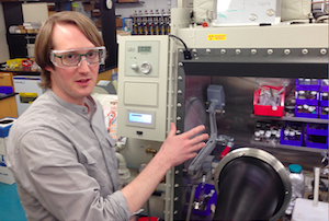 Assistant Professor of Chemistry James Blakemore, wearing safety goggles, stands next to equipment in his laboratory.