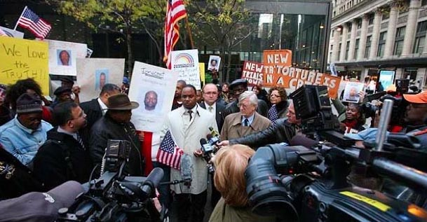 Photo: Jonathan Jackson (center left) stands with Atty. G. Flynt Taylor (center right) during a press conference on wrongful convictions outside a federal courthouse in Chicago in 2012. Wikimedia Commons photo.