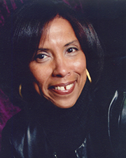portrait of Lynn A. King. She smiles widely and looks directly at the camera