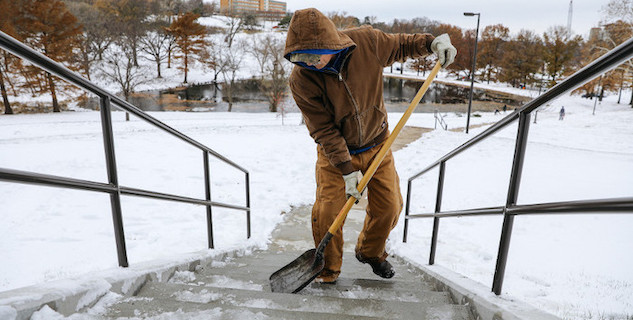 worker scraping snow and ice off of stairs